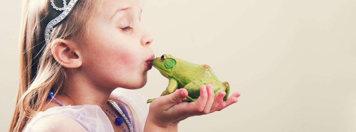 Mädchen als Prinzessin verkleidet küsst einen Frosch