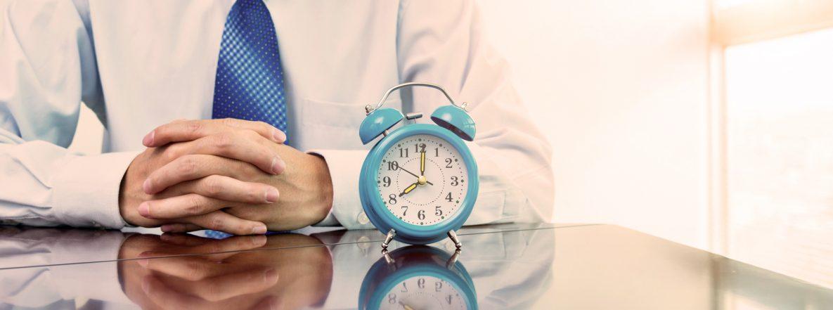 Wecker auf Schreibtisch und Businessmann im Hintergrund