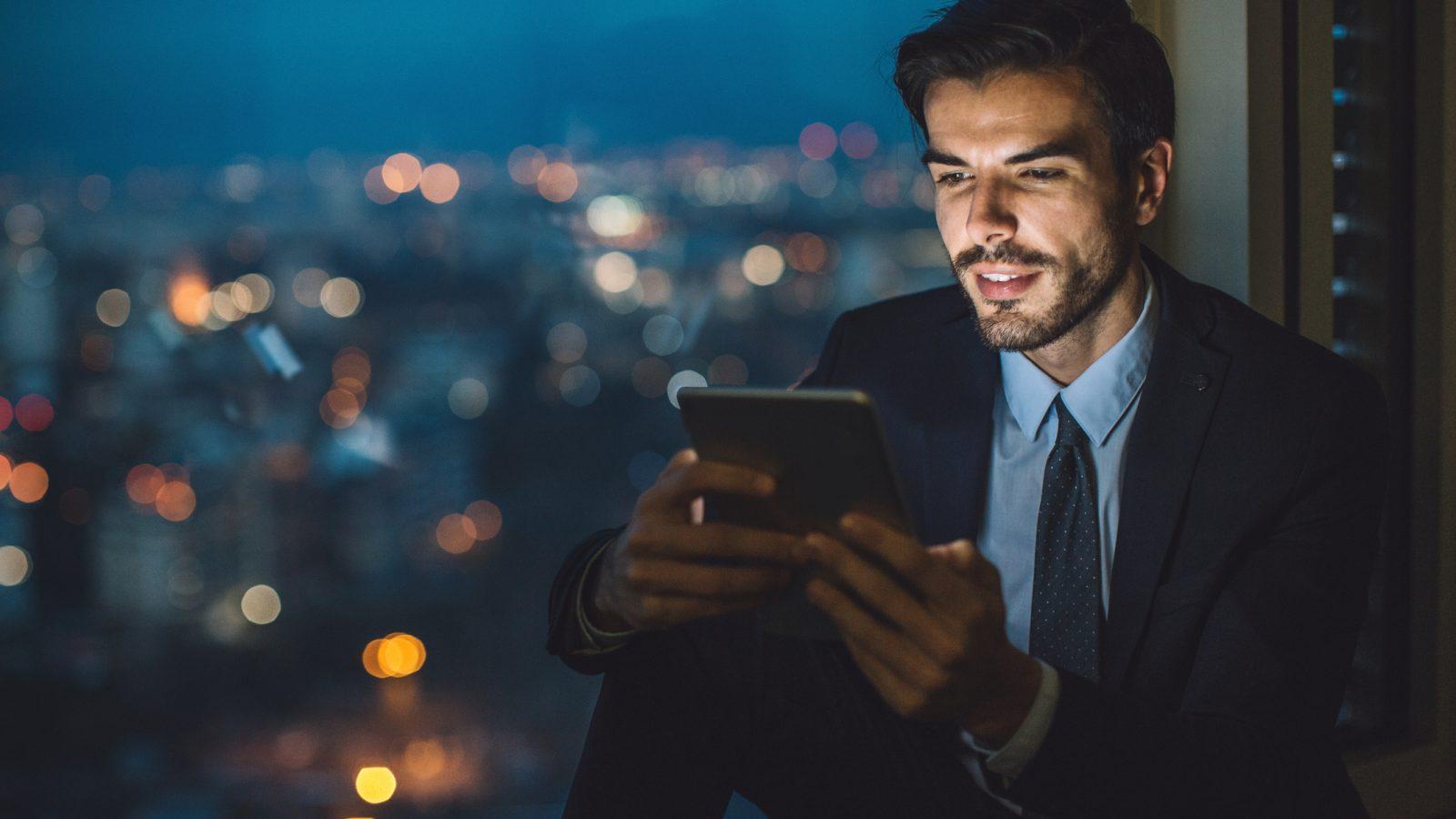 Mann liest Informationen von Tablet