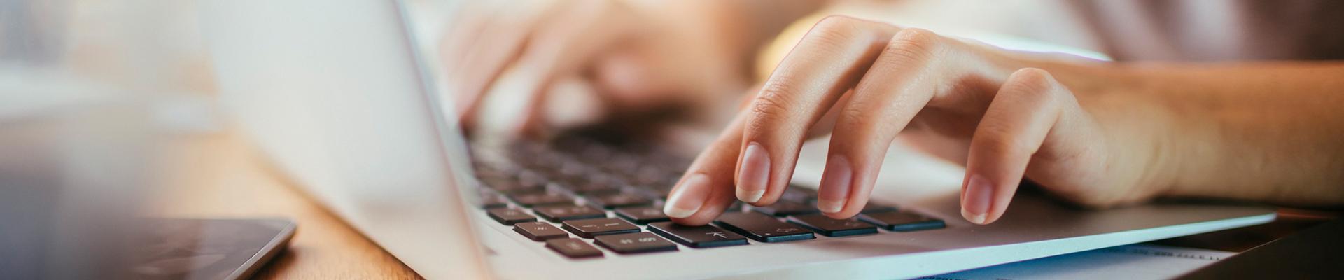 Laptoptastatur mit Frauenhänden